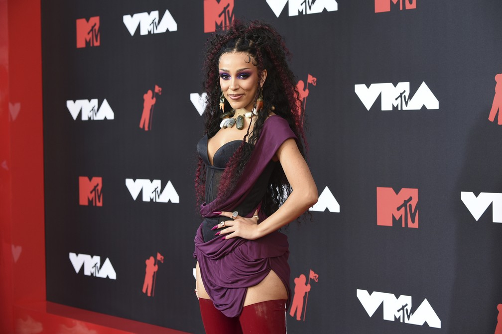 mulher preta está de pé no tapete vermelho, tem cabelo preto solto, top preto com sobreposição de tecido roxa e botas de cano longo vermelhas . Foto: Evan Agostini/Invision/AP. Post Looks icônicos do VMA e Met Gala 2021.