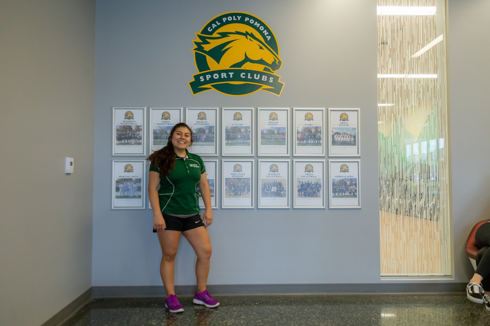 Arellano Rodriguez posing proudly in front of the Sport Clubs wall with club photos