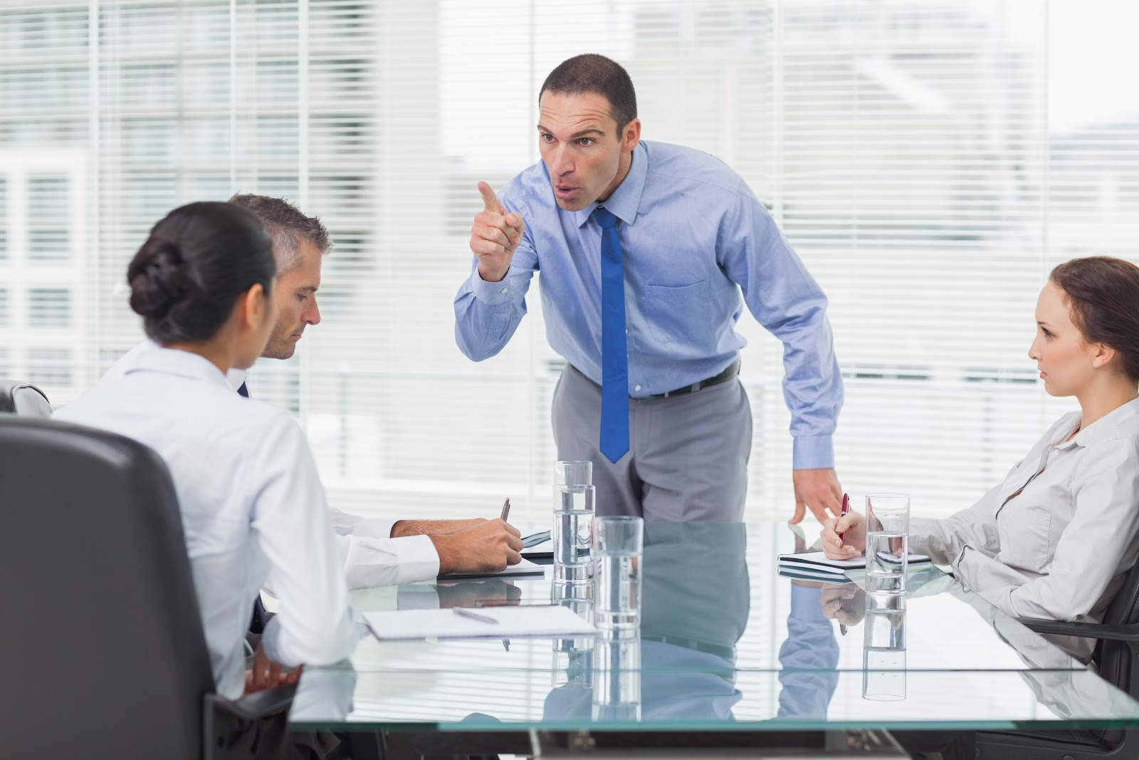 A man standing up in an office meeting pointing and yelling at coworkers