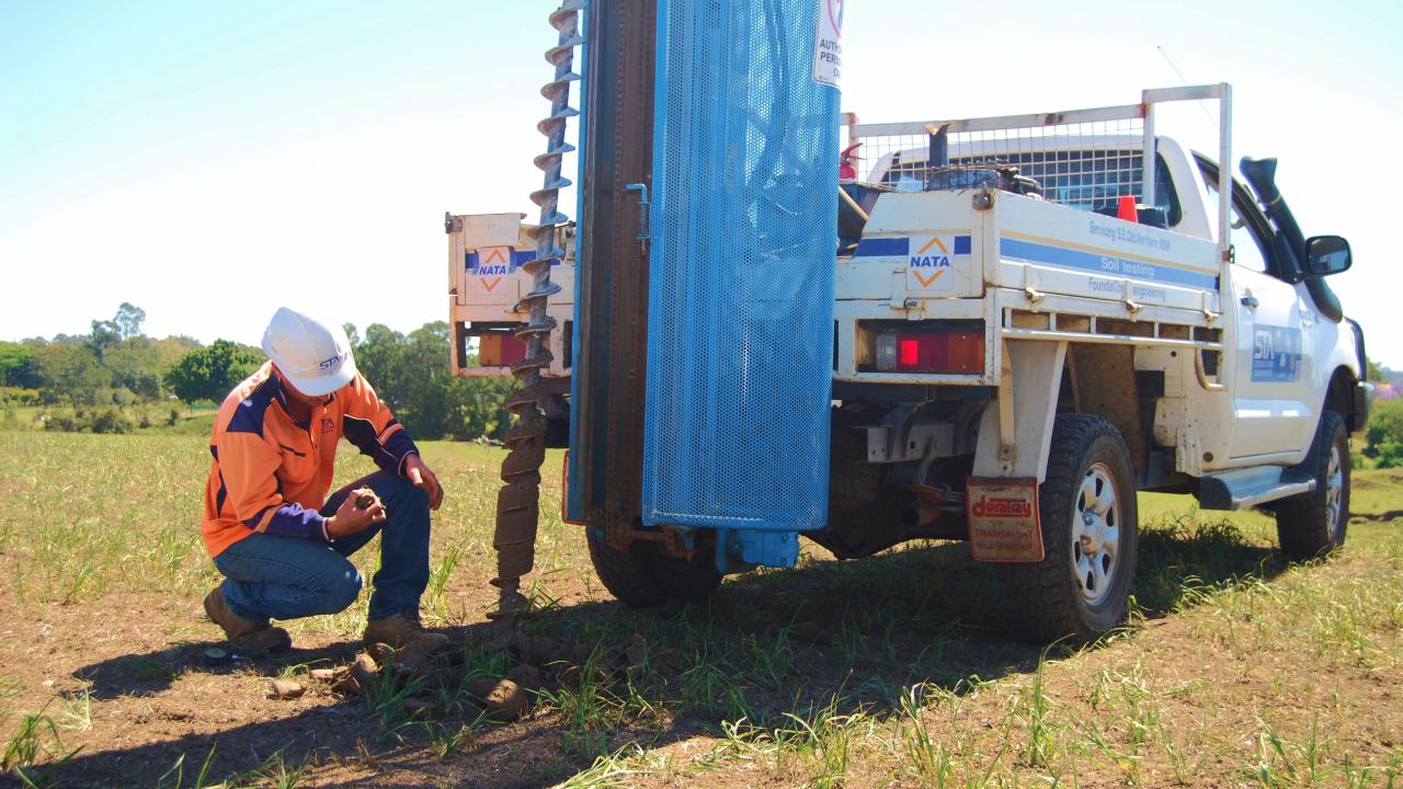 technician crumbling soil in hands beside 4wd vehicle