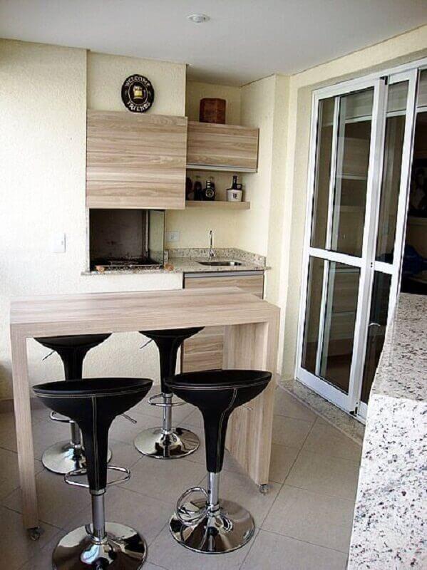 Varanda de apartamento com churrasqueira embutida, bancada de madeira com bancos pretos e armários de madeira.