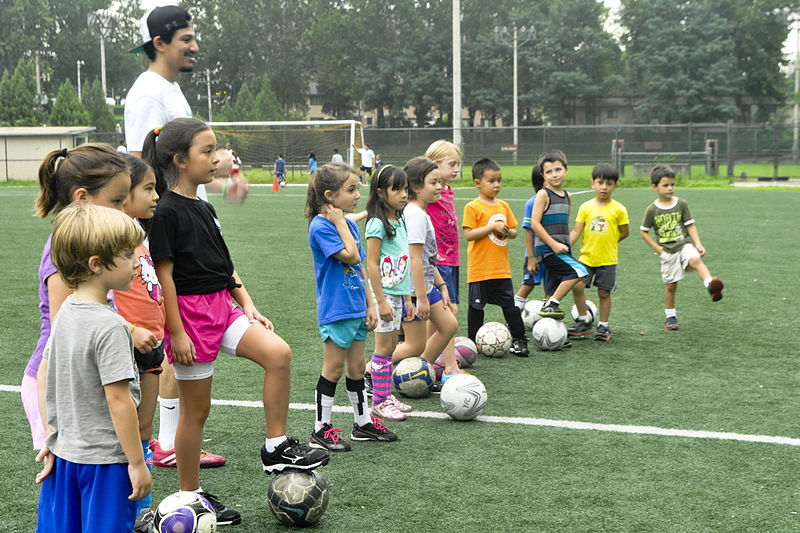 Kids lined-up with soccer balls and coach  (Soccer for 3 and 4-year-olds)