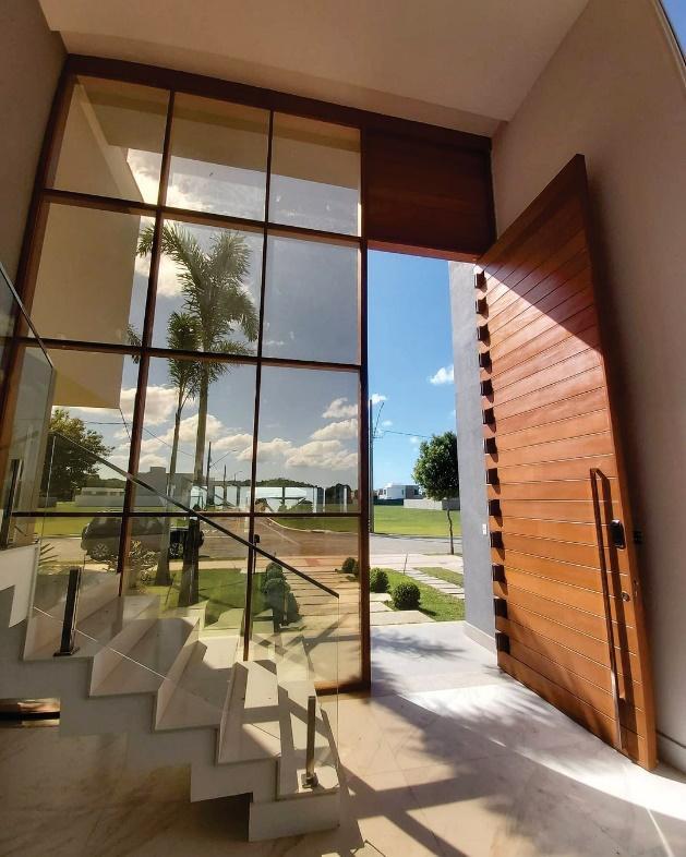Hall de entrada com porta grande de madeira, parede envidraçada e escada com porcelanato branco nos degraus