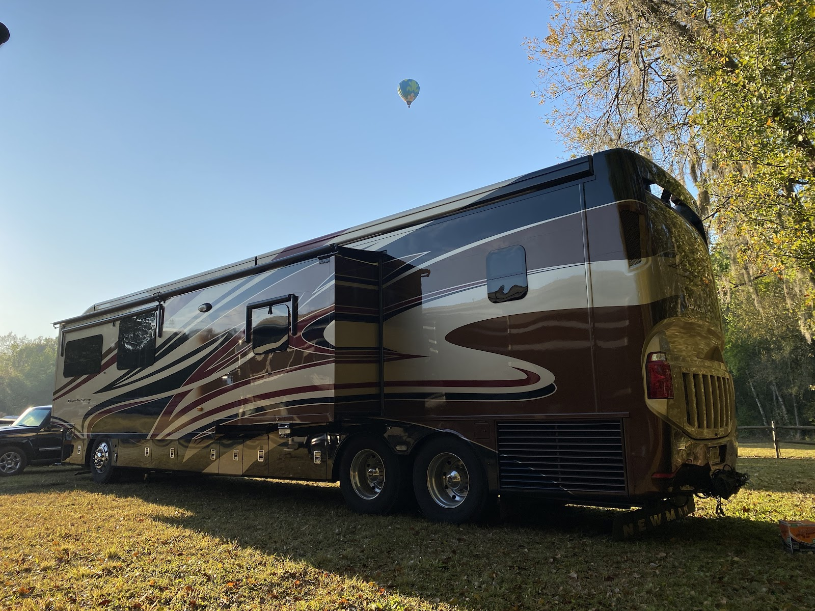 Class A RV parked with hot air balloons flying overhead