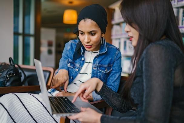Dua Wanita Melihat Dan Menunjuk Laptop Macbook