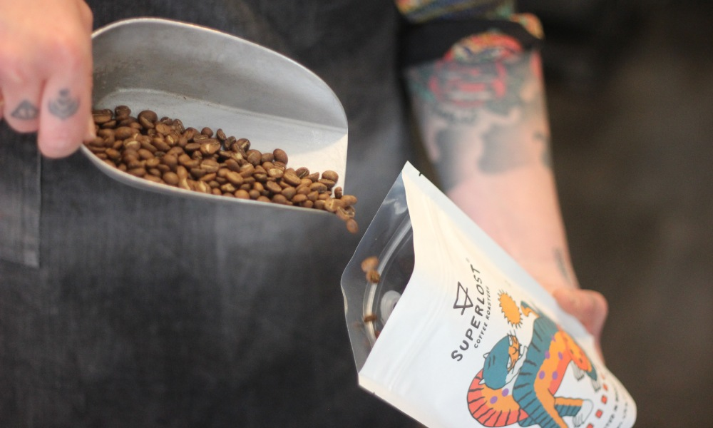 tipping roasted beans into sustainable coffee bag