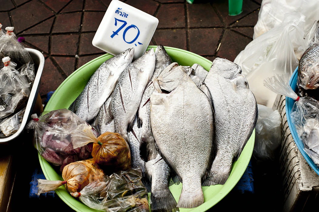 "Inexpensive food for sale at a Koh Samui market. A bowl of fish with a sign that says ""70 baht."""