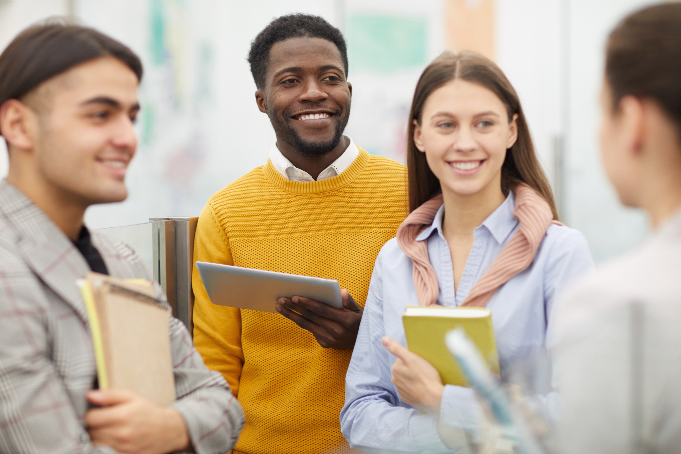 group of people smiling with notebooks and tablets