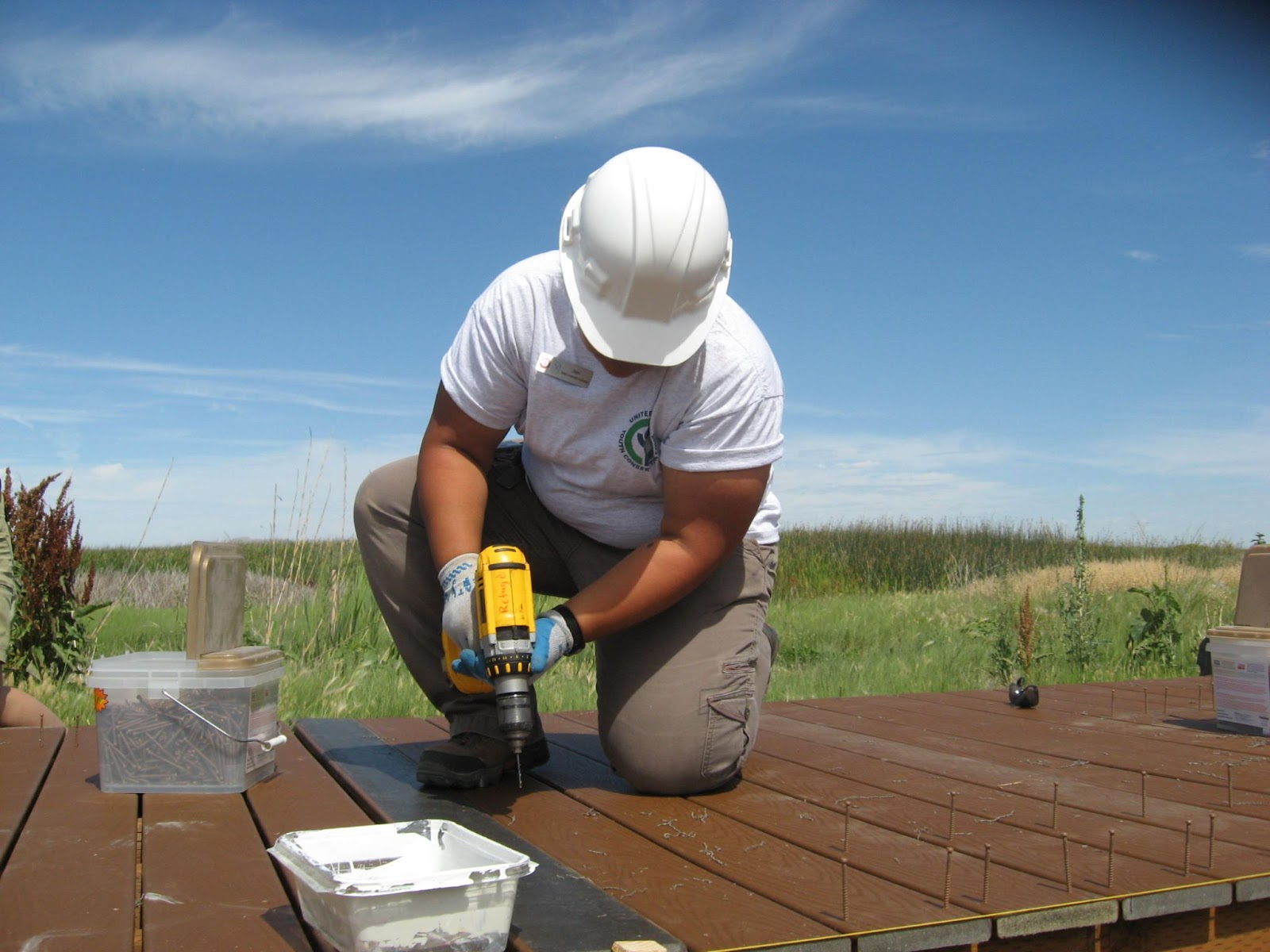 A youth corps worker constructs a bridge.