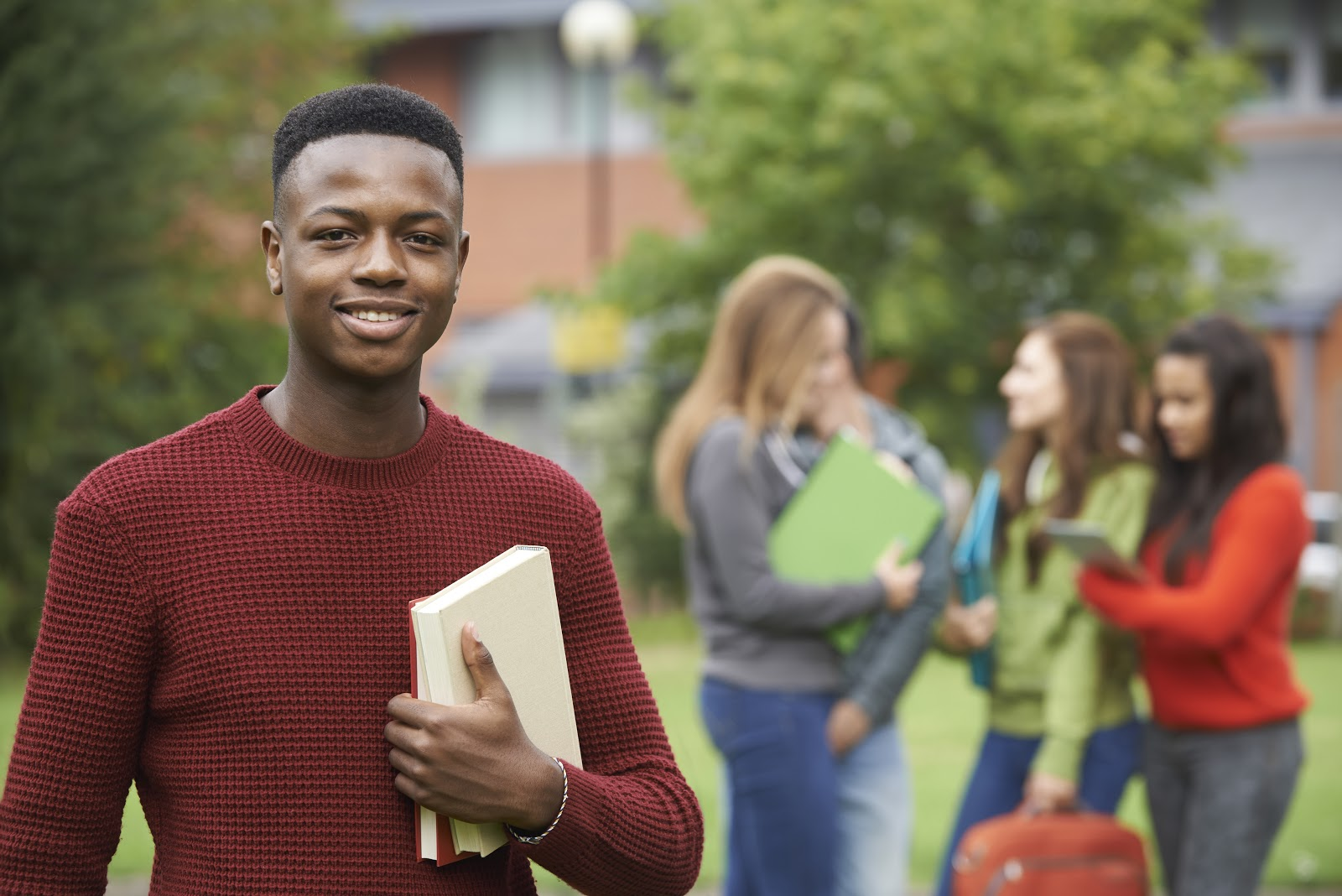 man smiling and holding a book