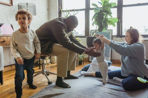 Multiracial family playing with children in casual outfit on textile on floor in light room near windows