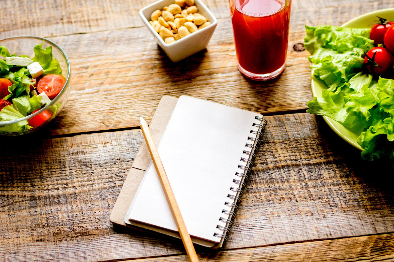 SCD diet: notebook resting on table with lettuce, nuts, and tea