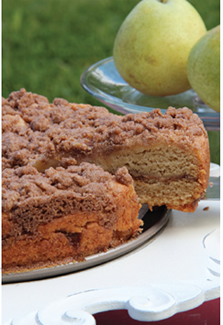 A round gluten-free coffee cake topped with apple cinnamon-sugar crumbles.