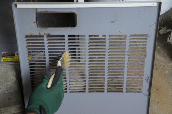 hvac technician cleaning dirty furnace