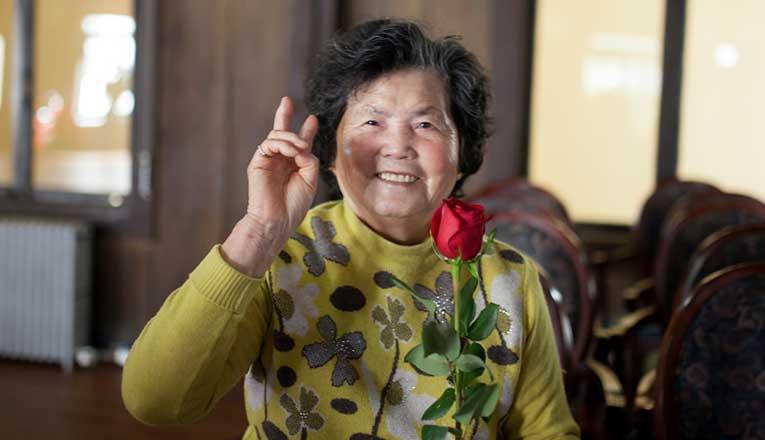 Older Lady Holding Red Rose Smiling