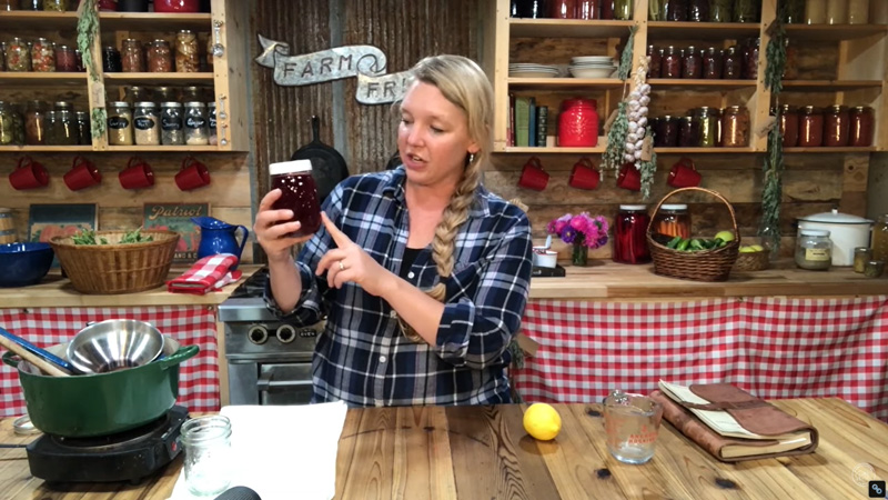 Woman in a kitchen holding a jar of homemade elderberry syrup.