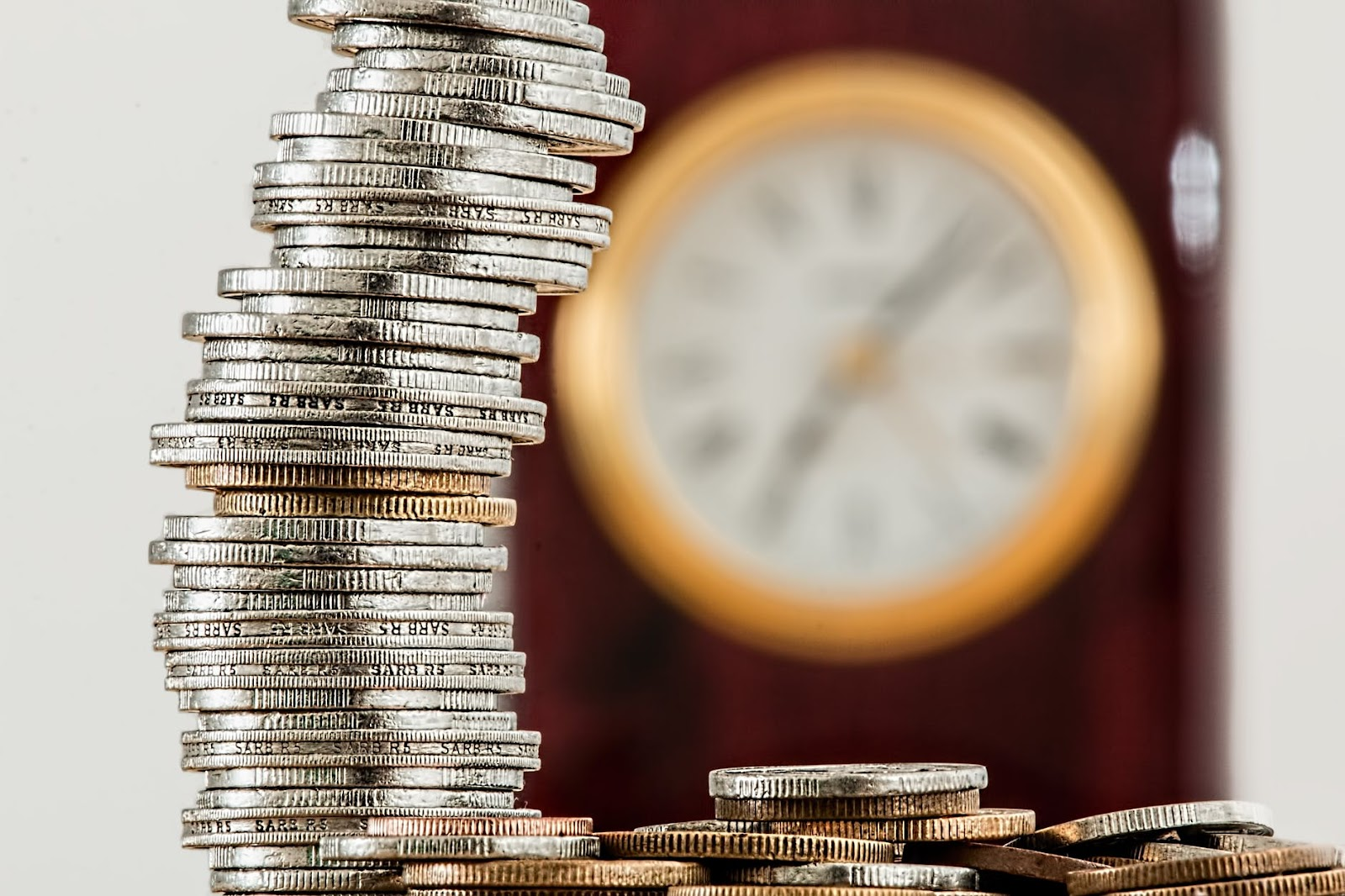 pile of coins with clock in background