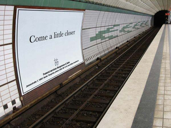 A Bergemann & Son Funeral Services billboard across a subway platform with the message 'Come a Little Closer'.