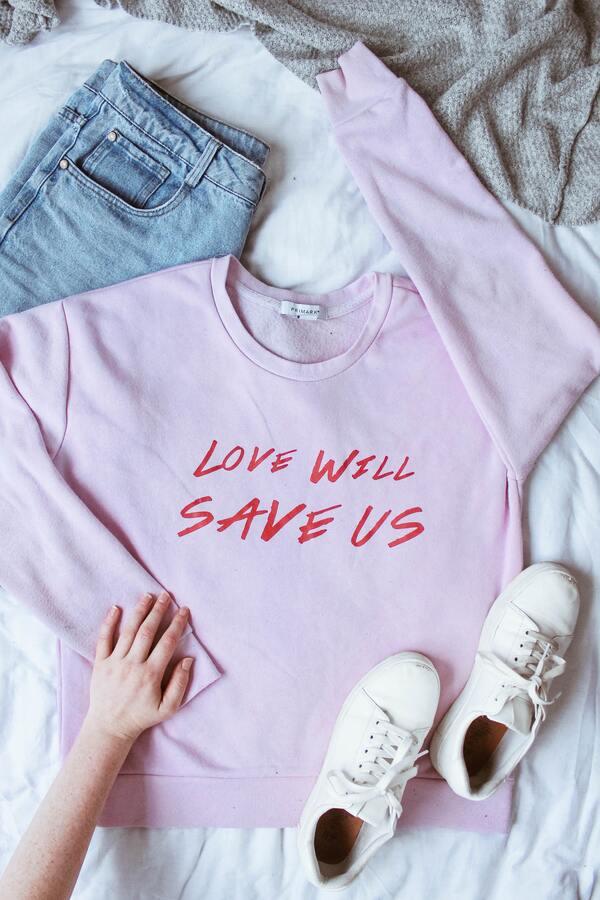 """foto de um look na cama com um moletinho escrito """"Love will save us"""", uma calça jeans e um tênis"""