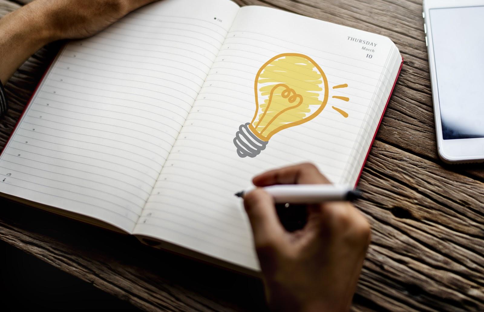 Um caderno com uma lâmpada desenhada.