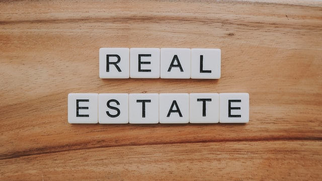 Letter tiles on wooden surface spelling out the words 'real estate'