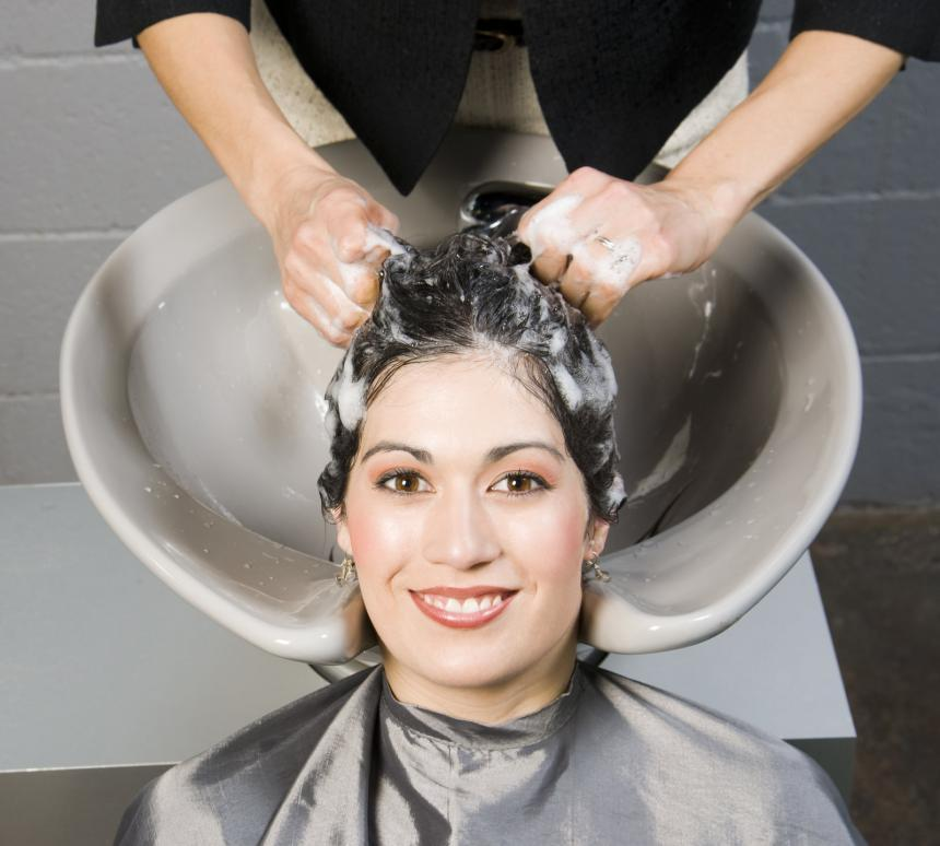 a woman getting her hair shampooed and conditioned at a salon