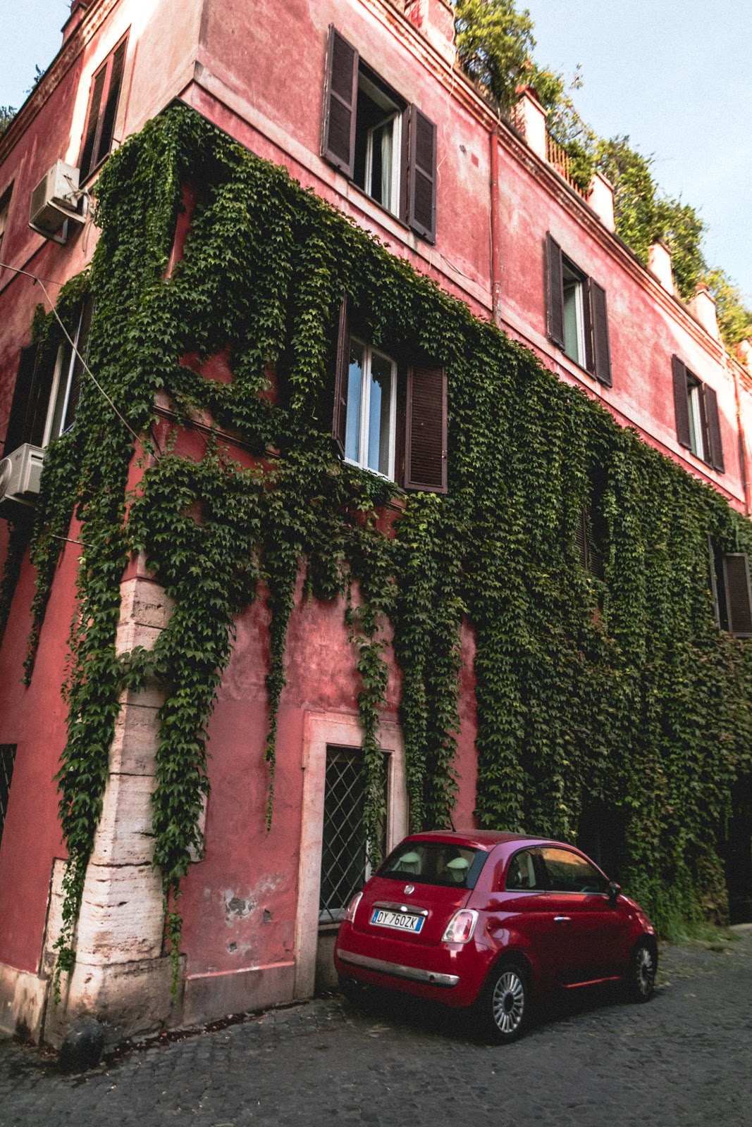 בניין אדום עם צמחיה מטפסת ומכונית אדומה לייד