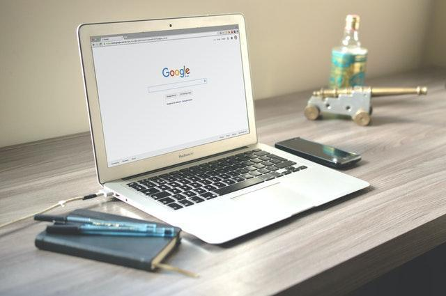 A laptop with Google opened up, next to a phone and a notebook