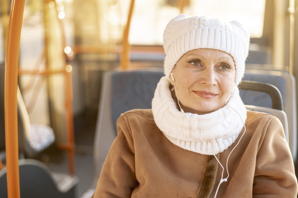 dame âgée assise dans un autobus avec une tuque et un foulard blanc en route vers sa maison de montréal