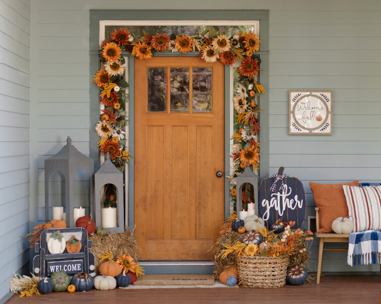 Porch decorated for fall with fall colored flower garland around the front door. A pumpkin that is painted blue and reads gather on it. basket of pumpkins and candles.