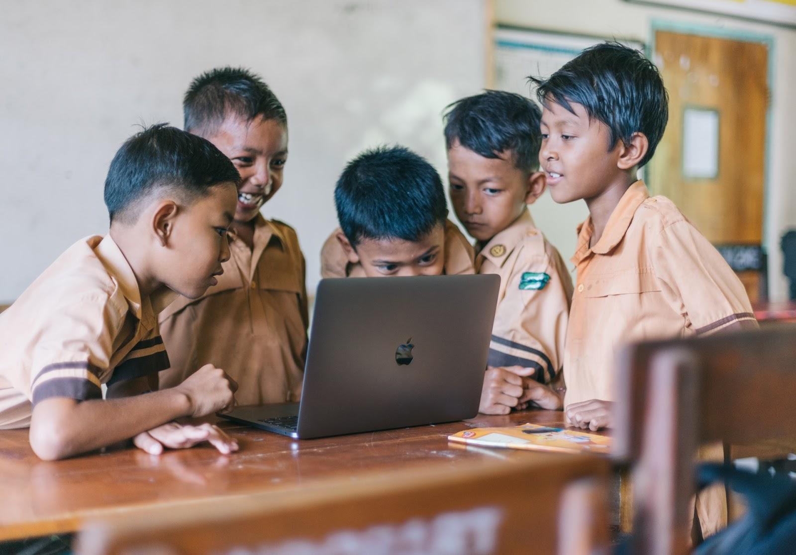 A group of five boys in school uniforms gather around a laptop in their <mark><mark><mark>classroom</mark></mark></mark>.