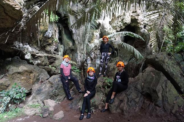 A group of people posing for a picture in a caveDescription automatically generated with medium confidence