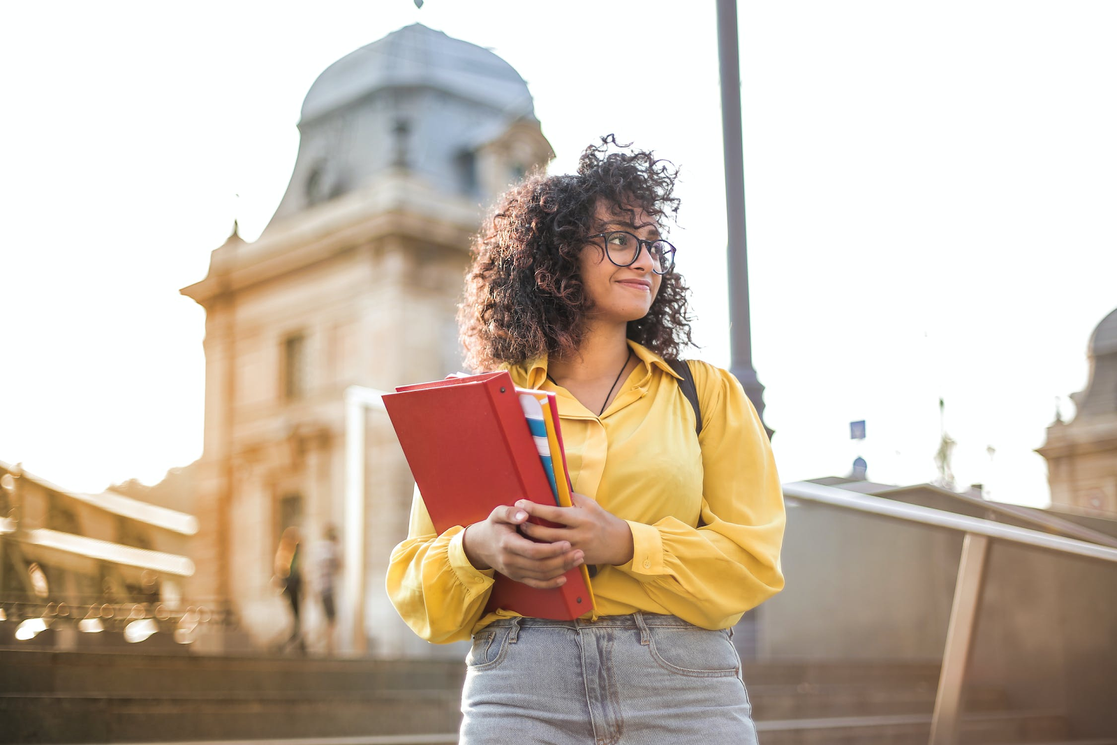Smiling woman in yellow standing outside and carrying a red binder