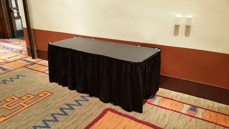 Example of 6 foot table skirted with black cloth and topped with black vinyl.