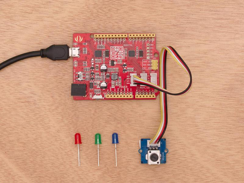 The Arduino board, mini USB cord and components in Thimble's Mini STEM Starter Kit are laid out on a wooden table.