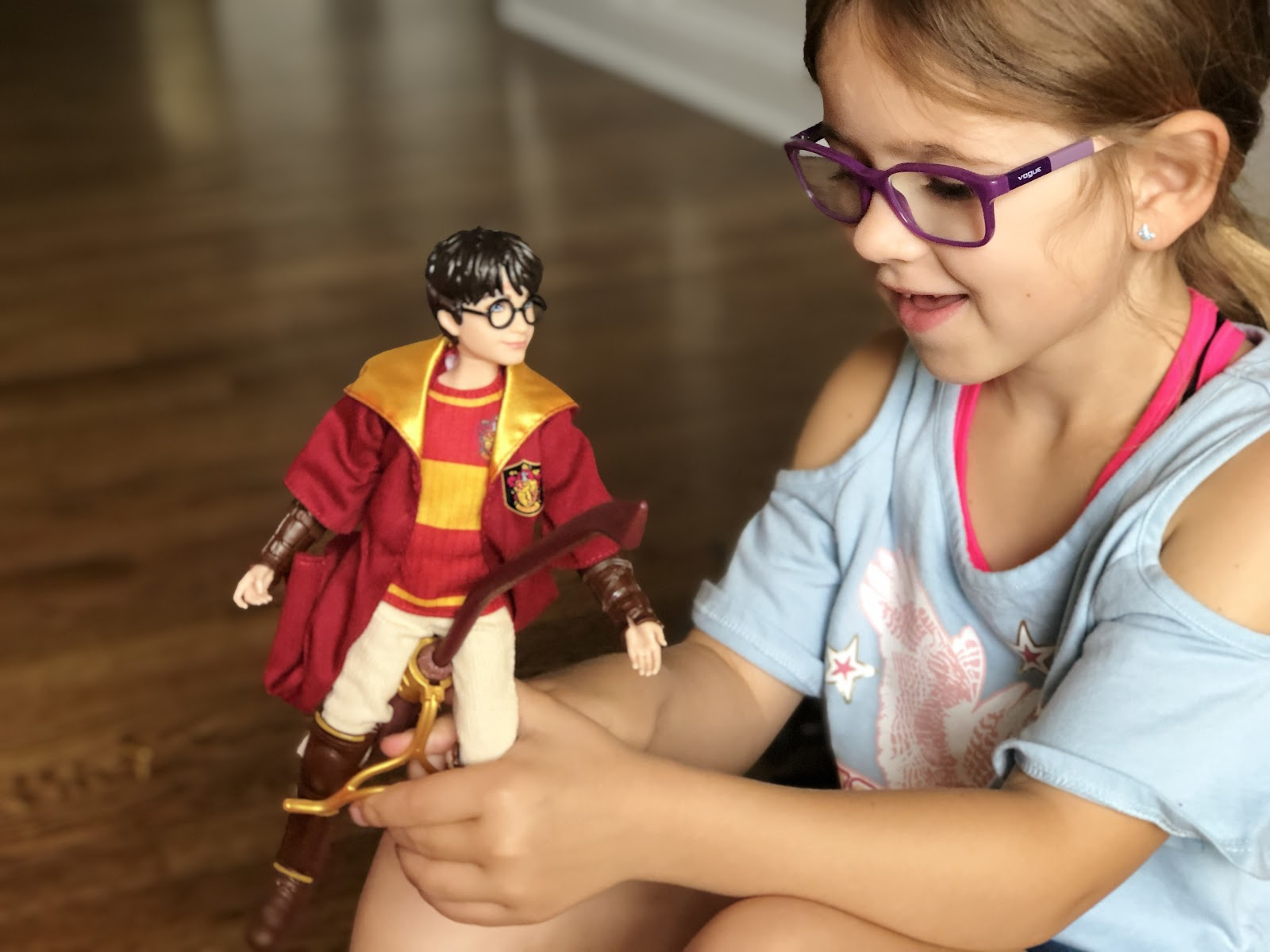 A girl playing with a Harry Potter action figure.