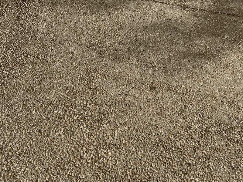 A close up of a driveway with a pebble aggregate finish where the concrete looks like it is made of small little pebbles.
