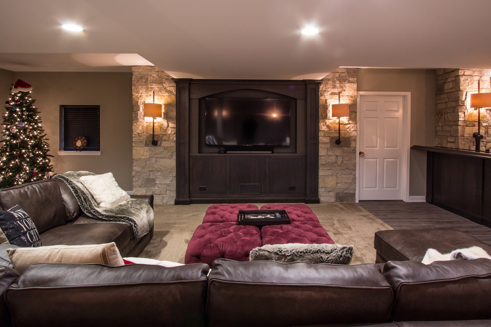 Basement media room with large wood and stone built-in TV, leather sectional and velveteen tufted ottomans.
