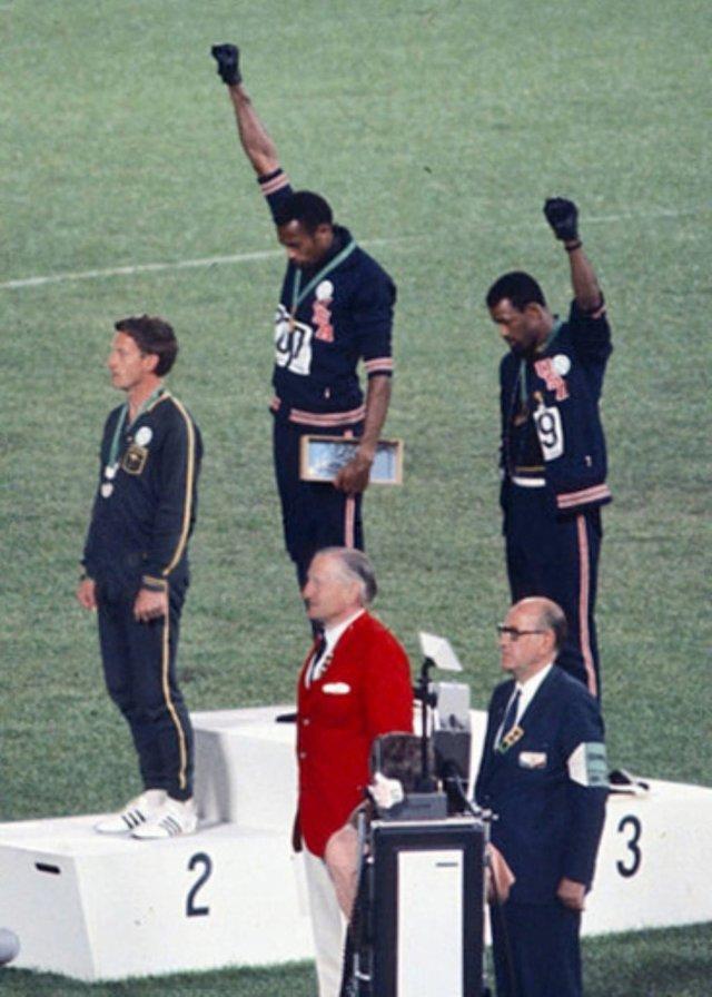 Atletas americanos fazem o gesto do