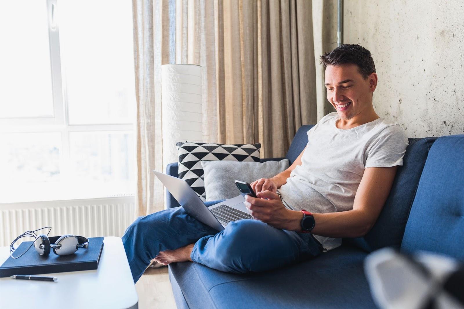 Homem sentado no sofá com celular na mão