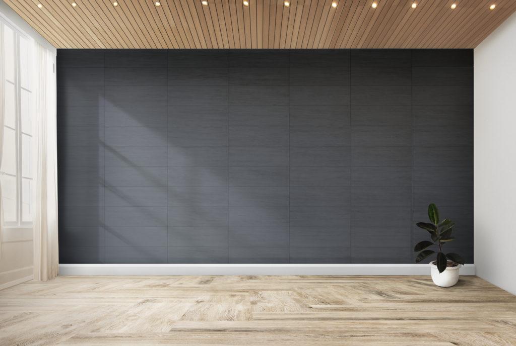grand mur gris noir avec plancher de bois pale et grande fenetre qui fait des rayons de lumiere dans la piece