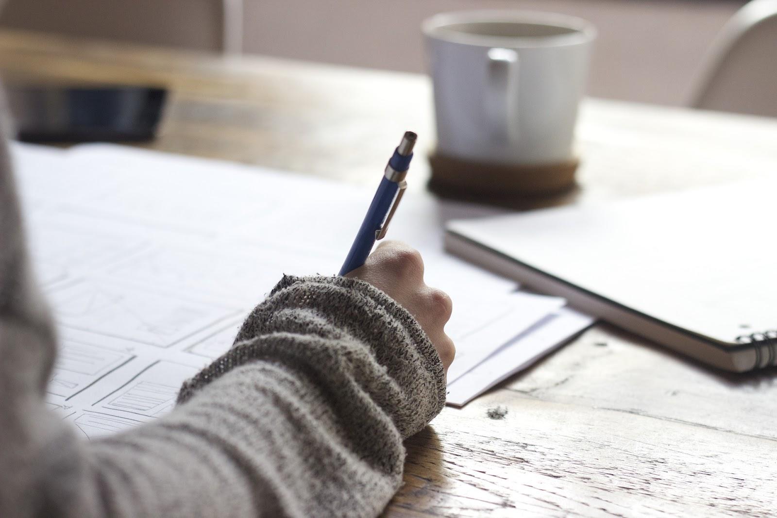 יד אישה כותבת עם ספל קפה ליד. במשרד
