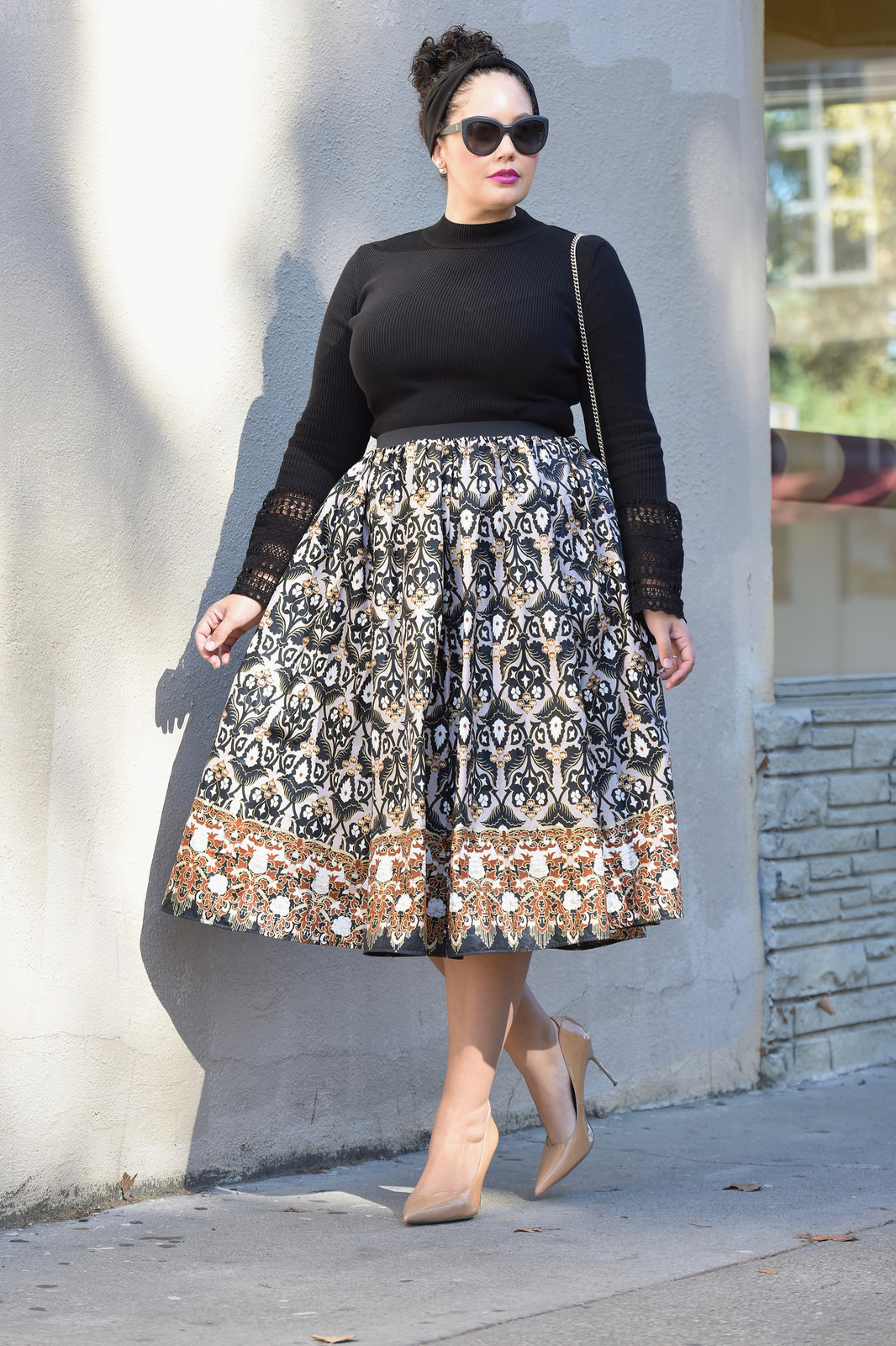 A woman is wearing a black turtleneck and patterned skirt