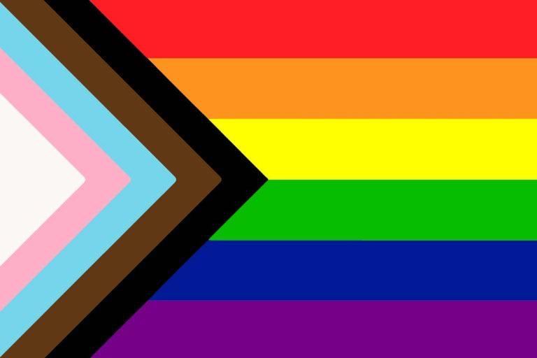 """Aktuální verze """"hrdé vlajky"""" se jmenuje Progress flag. Duha je doplněná o trojúhelník složený z bílého, růžového, světle modrého, hnědého a černého pruhu"""