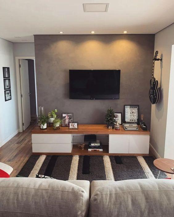 Sala com parede cinza, hack branca e marrom com objetos de decoração e sofá cinza.