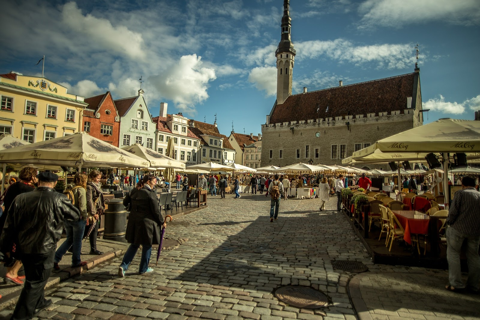 Tallinn old town, vibrant square full of outdoor restaurants and tourists wandering around. Large medieval cathedral in the background and traditional architecture.