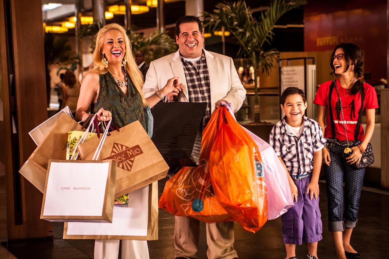 Família formada por pai, mãe e filhos saindo de shopping sorridentes e cheios de sacolas em mãos