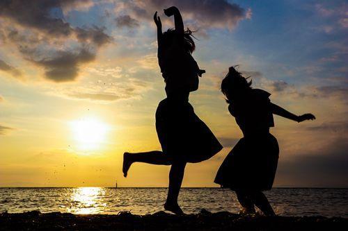焼けた空と浜辺で歓喜する二人のシルエット