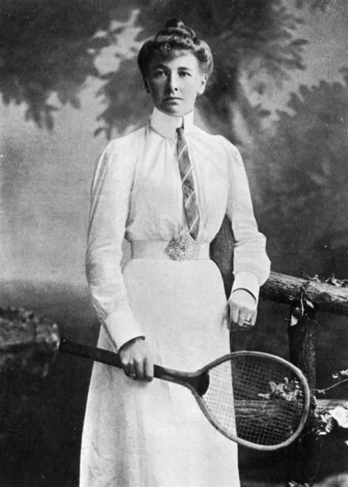 Imagem em preto e branco de uma mulher de pé com os cabelos presos, veste roupa branca e segura na mão direita uma raquete de tênis. Foto: www.olympics.org.uk.
