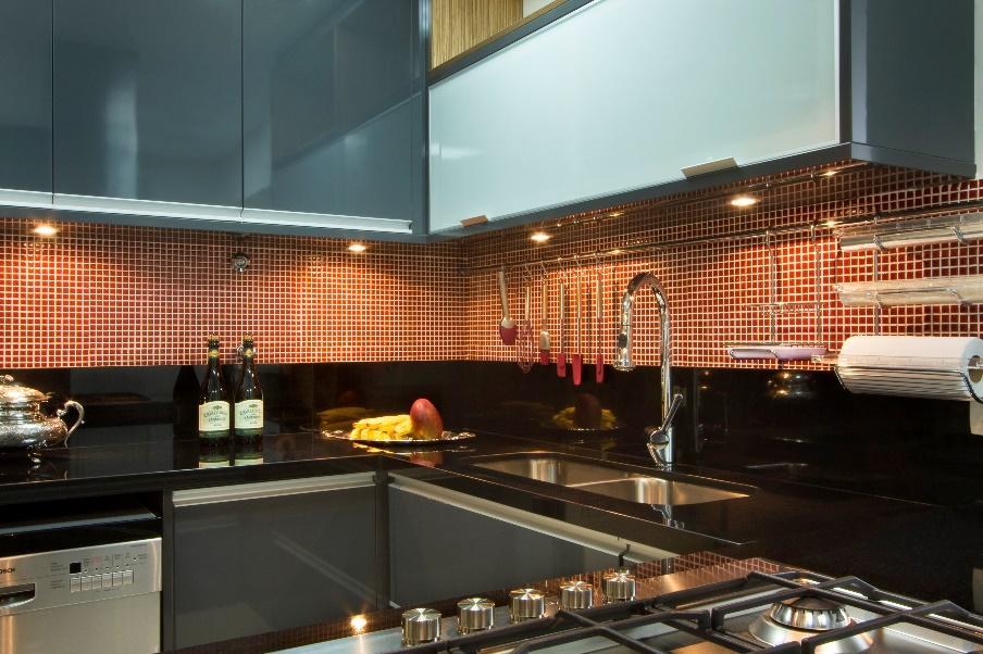 Cozinha com armários branco e cinza, bancada de mármore preta e parede revestida de pastilha laranja.
